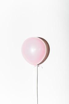 Close-up van roze ballon met schaduw die op witte achtergrond wordt geïsoleerd