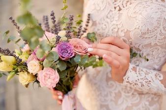 Close-up van roze en violet huwelijksboeket in de handen van de bruid