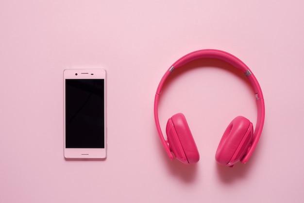Close-up van roze slimme telefoon met roze koptelefoon op een roze achtergrond. (bovenaanzicht). luisteren naar muziek