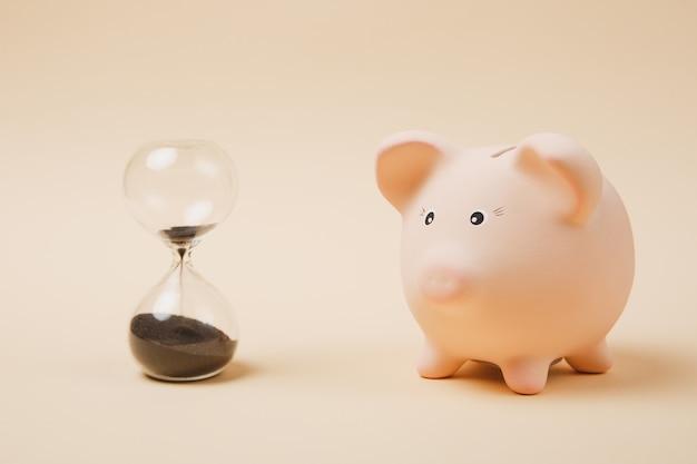Close up van roze spaarvarken en zandloper geïsoleerd op pastel beige muur achtergrond. geldaccumulatie, investeringen, bank- of zakelijke diensten, rijkdomconcept. kopieer ruimte reclame mock-up.
