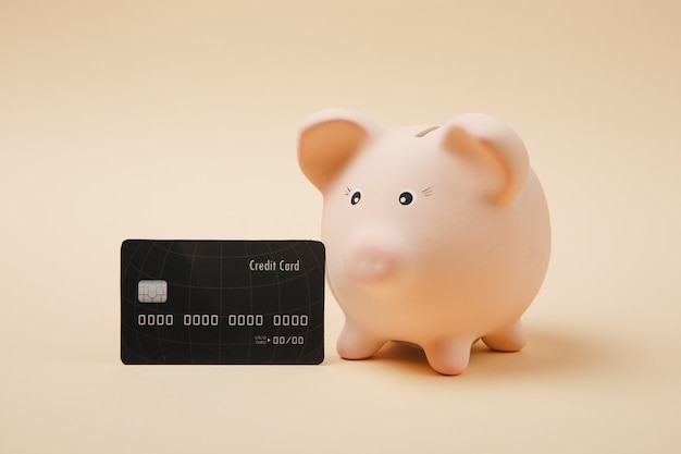 Close up van roze spaarvarken en zwarte creditcard geïsoleerd op beige muur achtergrond. geldaccumulatie, investeringen, bank- of zakelijke diensten, rijkdomconcept. kopieer ruimte reclame mock-up.