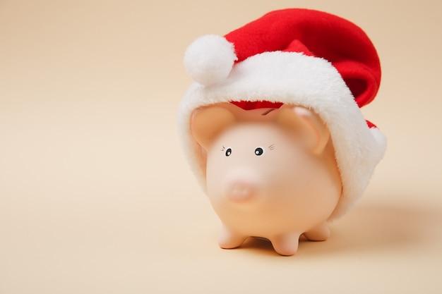 Close up van roze spaarvarken met kerstmuts geïsoleerd op pastel beige achtergrond. geldaccumulatie, investeringen, bank- of zakelijke diensten, rijkdomconcept. kopieer ruimte reclame mock-up.