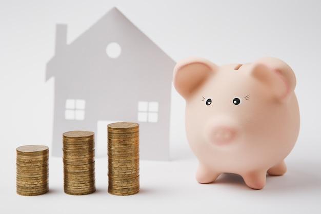 Close up van roze spaarvarken stapels gouden munten op witte muur achtergrond met huis. geld accumulatie investeringsbankieren of zakelijke diensten rijkdom concept. kopieer ruimte reclame mock-up.