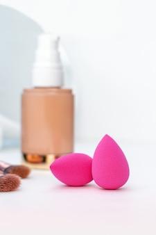 Close-up van roze spons en een fles beige cosmetische foundation, borstels voor make-up en spiegel, visagist en vrouwentoebehoren