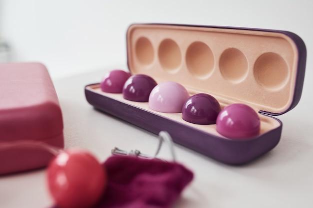 Close-up van roze vaginale ballen en stimulatoren die op tafel liggen. conceptie van imbuilding en de gezondheid van de vrouw.