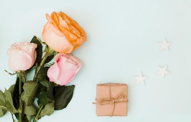 Close-up van rozen; geschenkdoos en uitgesneden drie sterren op gekleurde achtergrond