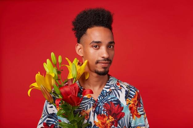 Close-up van rustige jonge afro-amerikaanse man, draagt in hawaiiaans shirt, kijkt naar de camera, houdt gele en rode bloemen, staat op rode achtergrond.