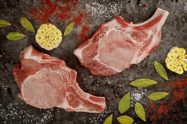 Close-up van ruwe varkenskotelettenrib met kruiden op grijze achtergrond. bovenaanzicht.