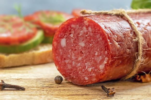 Close-up van salamiworststok op het snijden van een houten bord, schadelijk vet voedsel