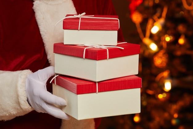 Close-up van santa in handschoenen met stapel geschenkdozen in zijn handen