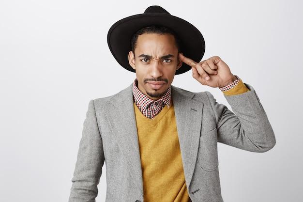 Close-up van sceptische afro-amerikaanse man op zoek met ontzetting, vinger over het hoofd rollen