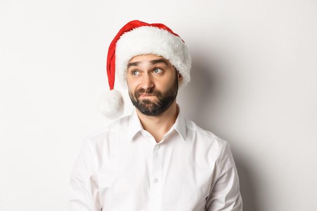 Close-up van sceptische man in kerstmuts op zoek twijfelachtig links, grimassen met aarzeling