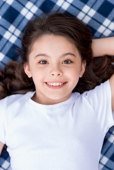 Close-up van schattig aantrekkelijk meisje liggend op deken