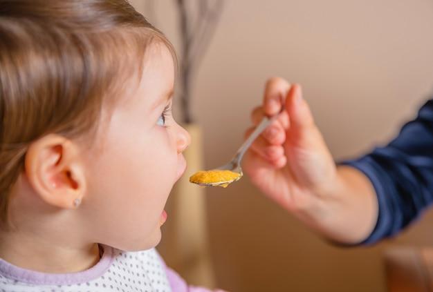 Close-up van schattig gelukkig babymeisje dat puree eet van een lepel in de hand van haar moeder thuis. selectieve focus op de puree.