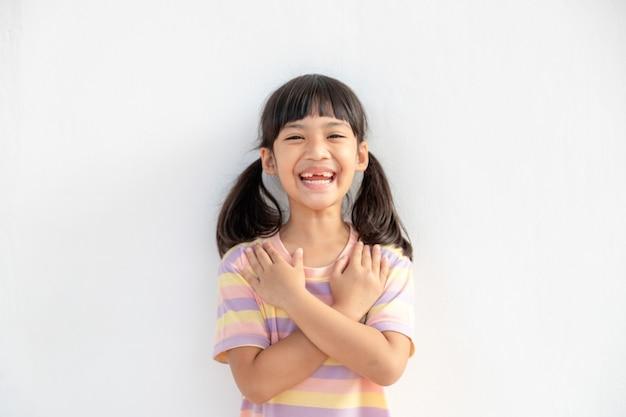 Close up van schattig gelukkig klein meisje geïsoleerd op een witte achtergrond hand in hand op hart borst voel dankbaar, glimlachend klein kind met gesloten ogen bidden dank god hoge krachten, geloof concept
