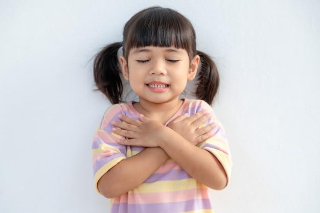 Close up van schattig gelukkig klein meisje geïsoleerd op een witte achtergrond hand in hand op hart borst voel dankbaar, glimlachend klein kind met gesloten ogen bidden dank god hoge krachten, geloof concept Premium Foto