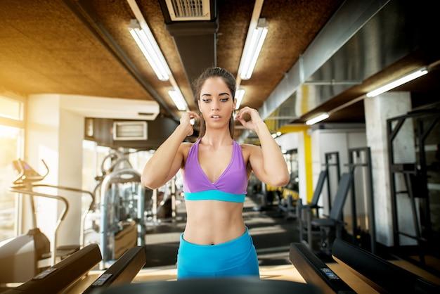 Close up van schattige aantrekkelijke jonge fitness meisje oefenen op de loopband in de zonnige, moderne sportschool.