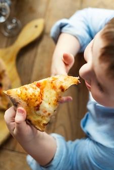 Close-up van schattige jongen pizza eten