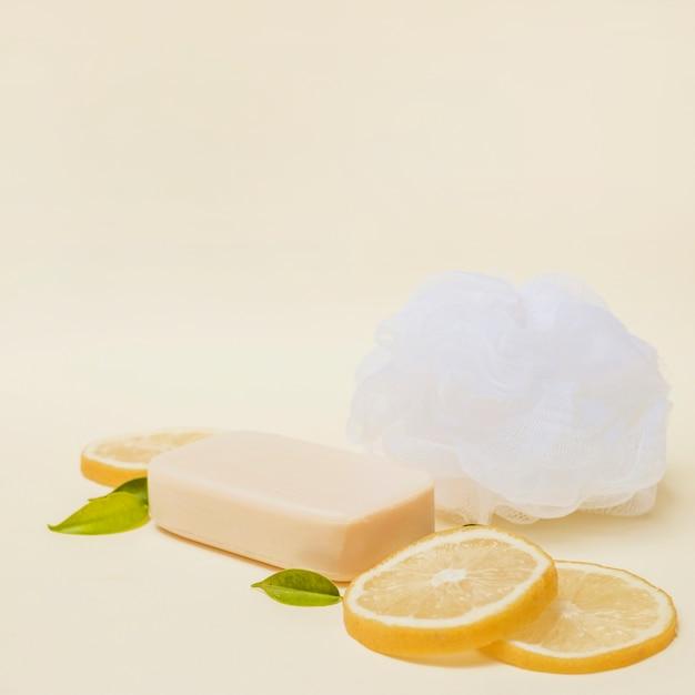 Close-up van schijfjes citroen; zeep en luffa op gekleurde achtergrond