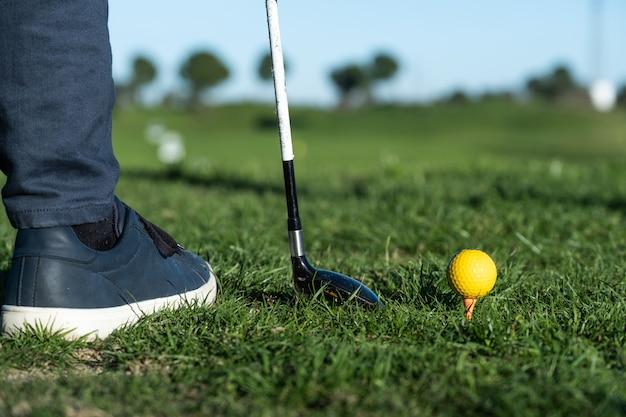 Close-up van schoenen, golfclub en golfbal op een driving range