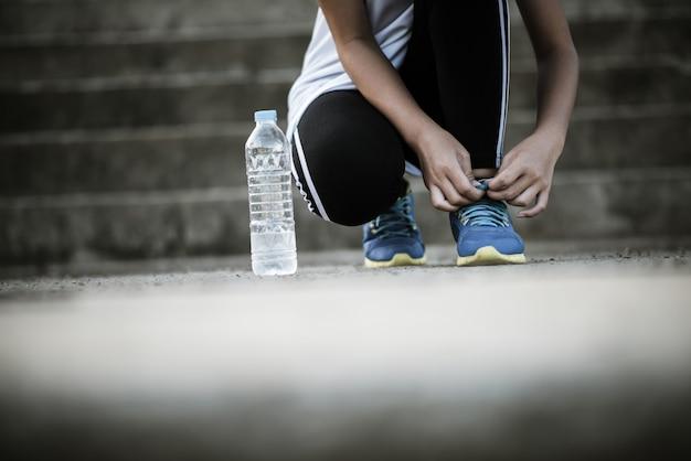 Close-up van schoenen vrouwelijke atleet koppelverkoop haar schoenen voor een jogging-oefening