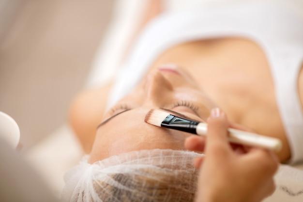 Close up van schoonheidsspecialist die cosmeticaborstel met gezichtsmasker neemt tijdens het werken