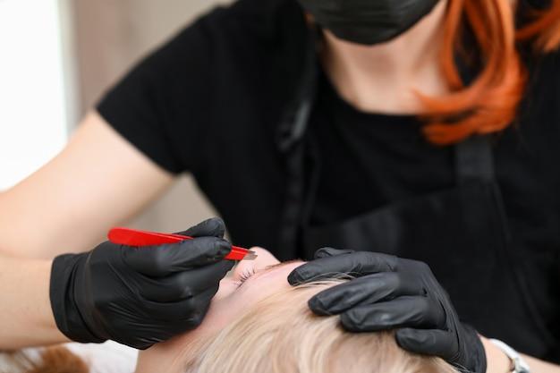 Close-up van schoonheidsspecialist die handschoenen draagt en wenkbrauwen met pincet plukt. salonarbeider die de wenkbrauwen van de vrouw voorbereiden op permanente make-up. mua en schoonheidsbehandeling concept