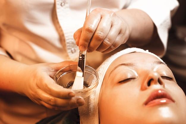 Close-up van schoonheidsspecialist hand doen een masker met hyaluronzuur met een borstel in een kopje om toe te passen op vrouwelijk gezicht.