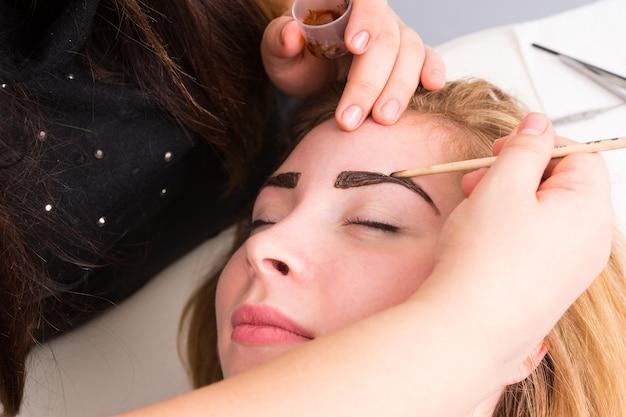 Close up van schoonheidsspecialiste die wenkbrauwen van vrouwelijke cliënt invult met donkerbruine make-up tijdens wenkbrauw spa-behandeling - blonde cliënt ziet er tevreden en ontspannen uit