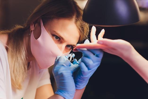 Close-up van schoonheidsspecialiste kleurrijke vernis toe te passen. nagellak op nagels aanbrengen met een penseel voor het aanbrengen van nagellak op de vingers. manicure nagelapplicator in een schoonheidssalon. vernis in een schoonheidssalon.