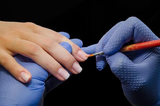 Close-up van schoonheidsspecialiste past gekleurde nagellak toe op een cliënt in een salon.