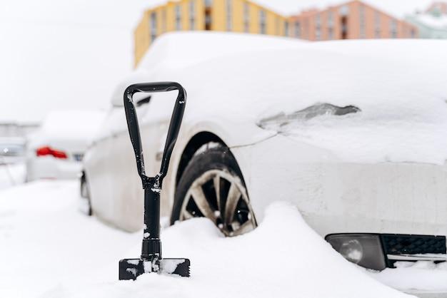 Close up van schop in de buurt van auto. auto wazig op de achtergrond. transport, winter, voertuig vast in de sneeuw. sneeuw verwijderen uit auto en transportconcept