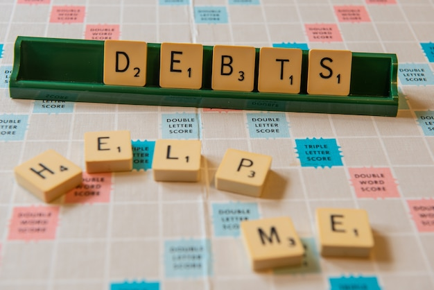 Close-up van schulden en help me geschreven op een scramble-bord onder de lichten