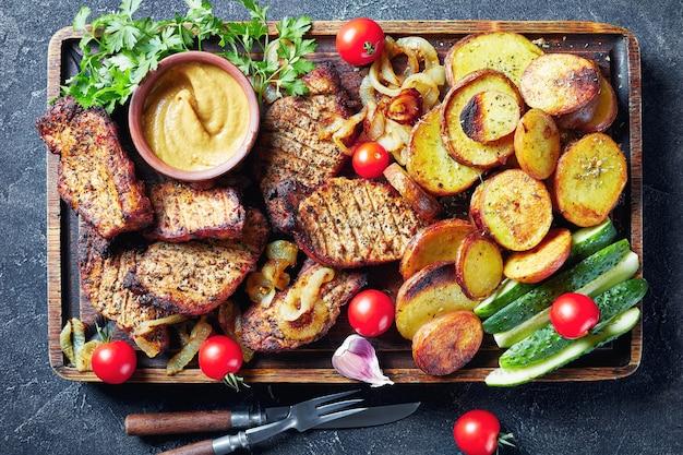 Close-up van schwenkbraten, sappige, rokerige gegrilde duitse varkenskoteletten worden gekookt op een swingende grill geserveerd op een ruwe snijplank met gesneden gebakken aardappelen, ui, tomaten en gesneden verse komkommer