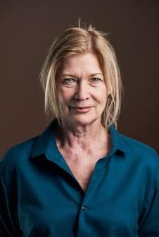 Close-up van senior blonde vrouw in blouse kijken camera geïsoleerd op zwarte background