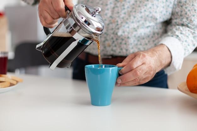 Close up van senior man gieten warme koffie uit de franse pers in de keuken tijdens het ontbijt. bejaarde die 's ochtends geniet van vers bruin café-espressokopje cafeïne uit vintage mok, filter ontspannen re