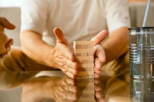 Close up van senior man handen doen zijn houten constructor thuis - concept van thuis studeren. kaukasisch mannelijk model zittend op de bank en werkend met stenen voor het trainen van fijne motoriek.