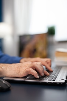 Close up van senior man handen typen op laptop toetsenbord oudere man ondernemer in thuiswerkplek ons...