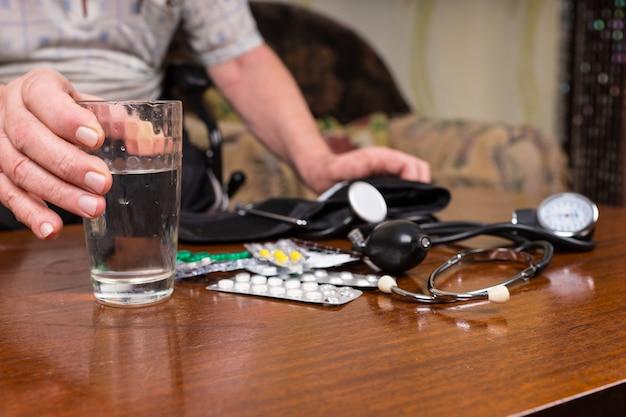 Close up van senior man met hart- en bloeddrukmedicijnen en medische benodigdheden verspreid over tafel
