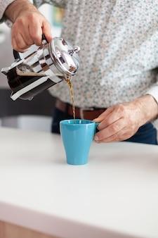 Close up van senior man morsen van warme drank na het bereiden van koffie met behulp van franse pers in de keuken voor het ontbijt. bejaarde die 's ochtends geniet van vers bruin café-espressokopje cafeïne uit mok