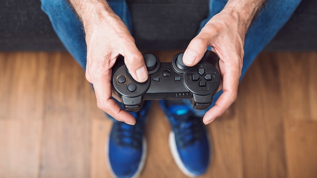 Close-up van senior man's hand met video game console