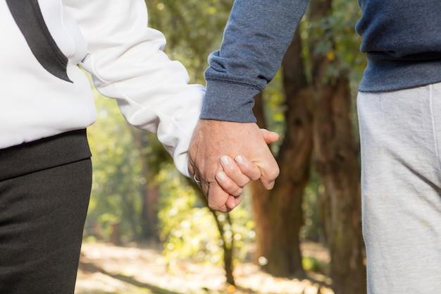 Close-up van senior paar hand in hand en wandelen in het bos