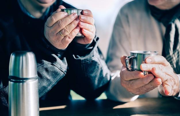 Close up van senior paar handen met kopjes met warme koffie over een houten tafel