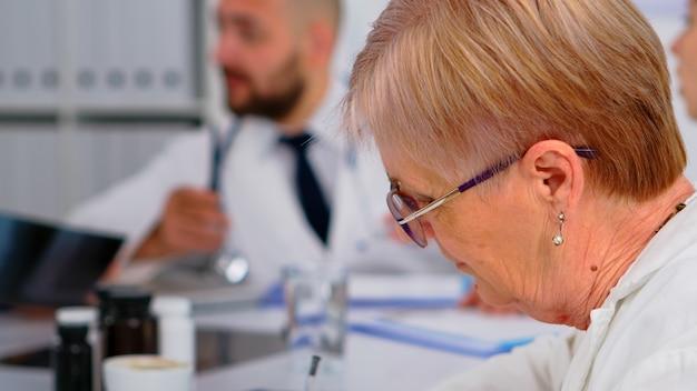 Close up van senior vrouw arts in gesprek met collega tijdens medische conferentie zittend op het bureau in het kantoor van de ziekenhuisvergadering. bespreken over ziektesymptomen in de kliniekruimte tijdens brainstormen