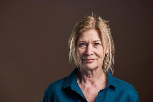 Close-up van senior vrouw met blond haar en in blouse kijken camera geïsoleerd op zwarte background