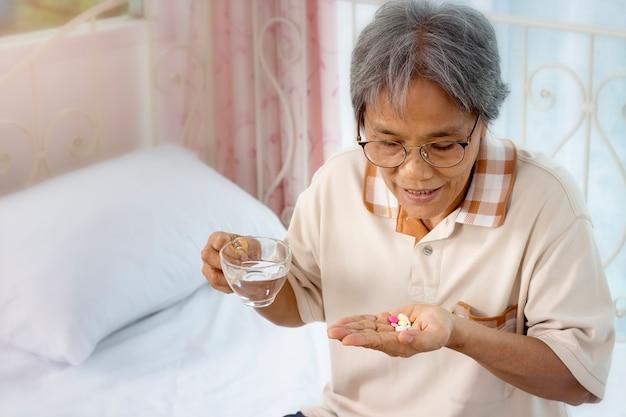 Close-up van senior vrouw met pillen en glas water thuis