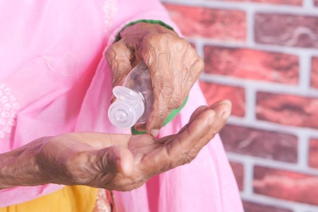 Close-up van senior vrouwen hand met behulp van ontsmettingsgel om virus te voorkomen