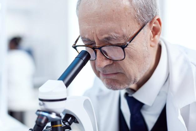 Close up van senior wetenschapper die virusmonster analyseert met behulp van een microscoop in een moderne faciliteit. chemicus-onderzoeker in steriel laboratorium die experimenten doet voor de medische industrie met behulp van moderne technologie.