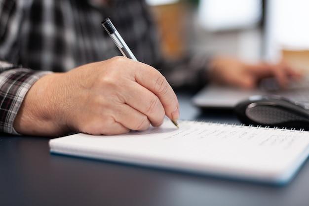 Close up van senior zakenvrouw schrijven van notities