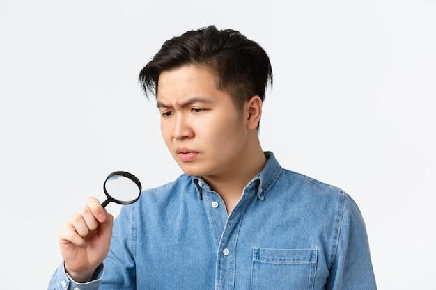 Close-up van serieus ogende gefocuste aziatische man die iets bestudeert dat zoekt met een vergrootglas-looki...